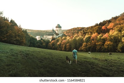 A man in a park with a dog with a stunning view of the underwater sunset, Karlstejn gothic castle near Prague, the most famous castle in Czech Republic, autumn season