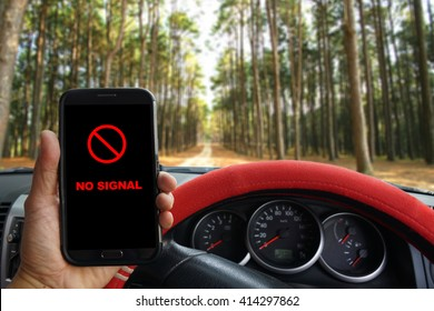 Man parking the car to use smartphone  with showing NO SIGNAL icon, sunshine and evening sky in the forest, used for safety concept