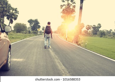 A man parking his car on the road and carrying backpack to continue walking.