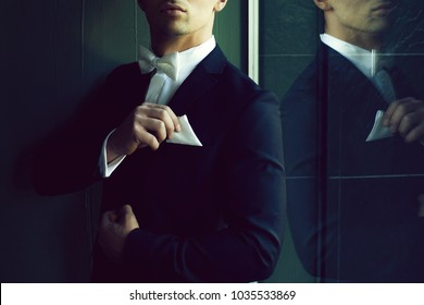 Man part of face in suit with white bow tie touches handkerchief young elegant stylish turns sideway and reflects in mirror on grey background