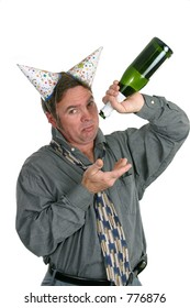 A man in a party hat holding an empty champagne bottle and looking sad.