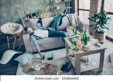 Man, party maker having hangover after stag party, sleeping on sofa, holding bottle of beer with chaos in the messy living room after night party