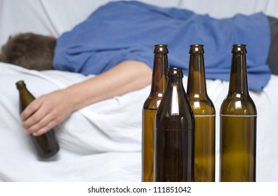 Man passed out with a beer bottle in his hand. Alcohol abuse