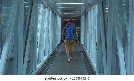 Man passenger with backpack boarding an Airplane via Docking Sleeve.