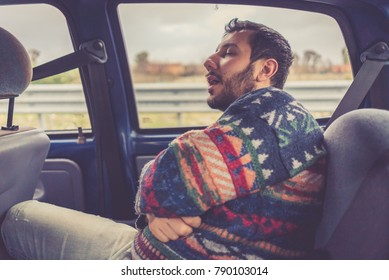 man passenger sleeping in the backseat of a car on a trip