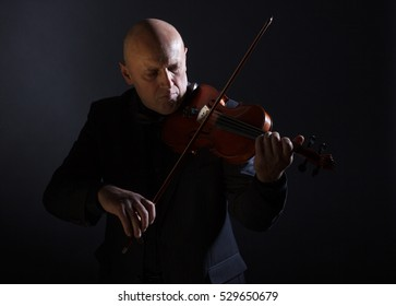 A man passionately playing the violin on dark background.