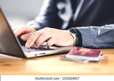 Man with passport and laptop. Travel document and identification. Immigrant writing electronic application for citizenship. Apply for digital visa. Online flight ticket or web check in.