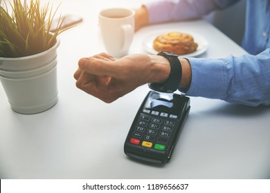 man paying bill with smartwach at restaurant
