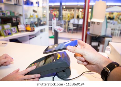 Man paying bill through smartphone using mobile payment