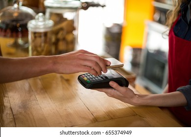Man paying bill through smartphone using NFC technology in cafe