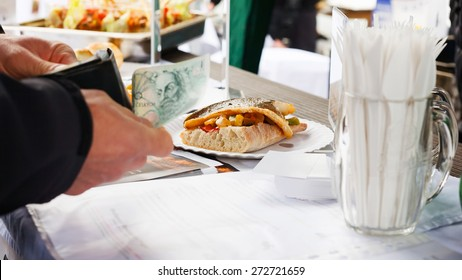 Man paying for a fresh sandwich at the market
