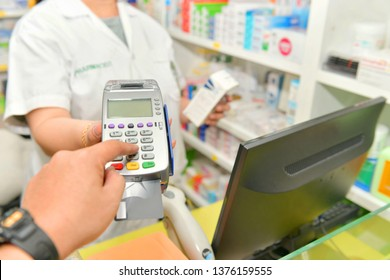 Man paying for Medicaments with credit card in pharmacy drugstore.