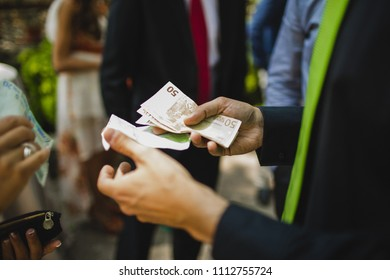 Man paying money bills to a woman in euros