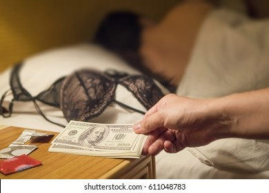 Man paying money dollar to sleeping prostitute woman on white bed in hotel