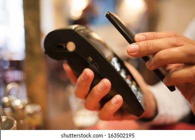 Man paying with NFC technology on mobile phone, in restaurant, bar, cafe