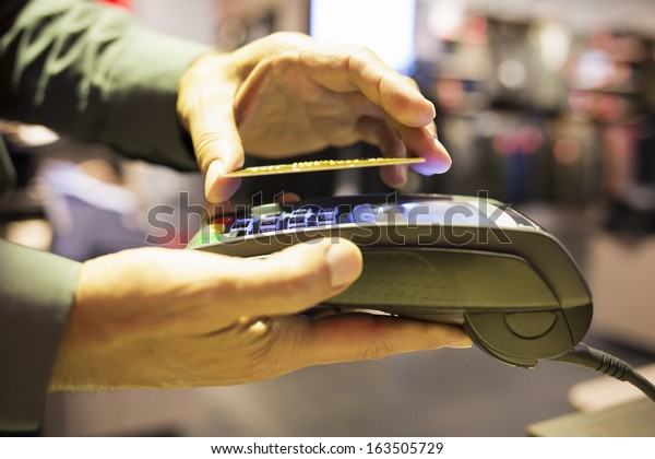 Man paying with NFC technology on credit card, in clothing store