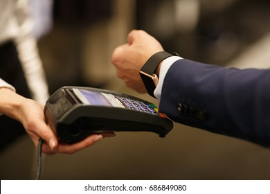 Man paying with NFC technology with smart watch application in clothing store, close-up, point of view, shallow depth of field