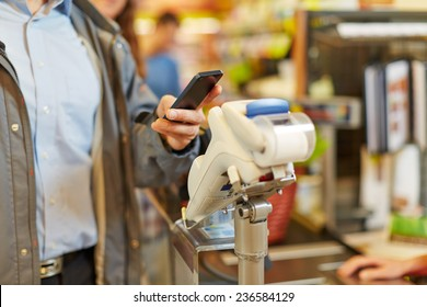 Man paying wireless with his smartphone at supermarket checkout