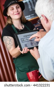 Man pays cafe bill and tip by signing with finger for credit card on a tablet