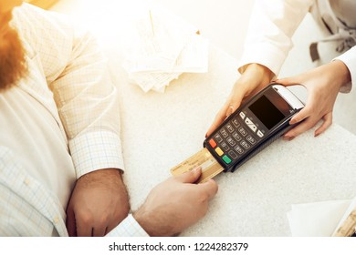 A man pays his order in a cafe with a bank card. Top view of payment for coffee and food in a coffee shop by credit card. The concept of restaurant business and the quality of customer service