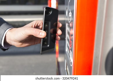 Man pays his transport ticket with his mobile phone on platform station. NFC. Contactless