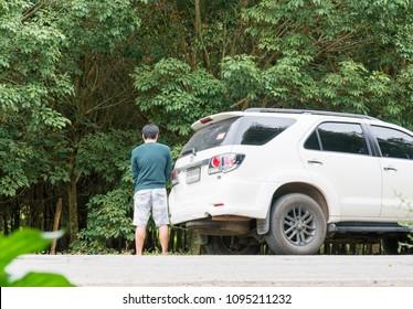 man pee near car on forest near road.