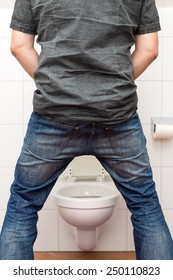 a man peeing standing up in the restroom