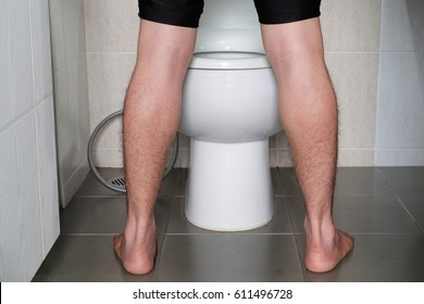 Man peeing to toilet bowl in restroom from back Health concept