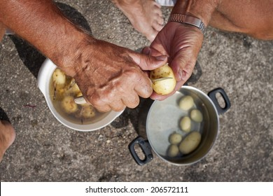 A man peeling early potatoes with a knife outdoors in Sweden, Scandinavia