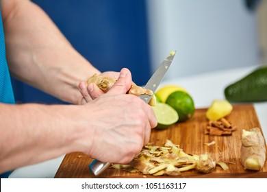 Man peeling ginger on a wooden board
