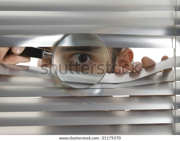 A man is peeping through the blinds with a magnifying glass.