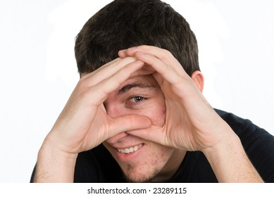 A man peering through his hands isolated on white.