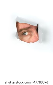 A man peers through a torn paper hole.