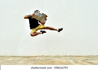 Man performing a flying kick while he reads the newspaper