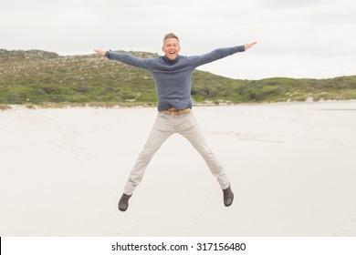 Man performing a jumping jack at the beach