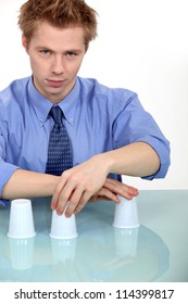 Man performing trick with three cups