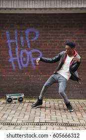Man performing urban dance near boombox and wall with graffiti.