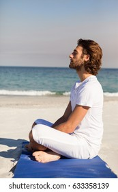 Man performing yoga at beach on a sunny day