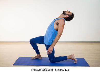 Man performing yoga in gym
