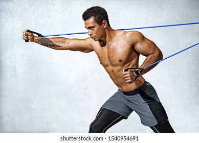 Man performs exercises with expander. Photo of sporty man workout on grey background. Strength and motivation