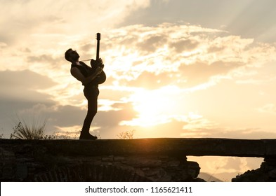 Man performs on electric guitar on old Roman aqueduct during sunset.