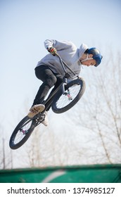 A man performs tricks in the air on a bicycle in the skatepark