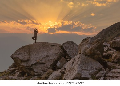 A man performs Yoga (vrikshasana - Tree pose) on a rocky mountain cliff at Deo Tibba trek in Manali, Himachal Pradesh. Serene view of sunset, clouds & sun rays. Summer Hiking in Himalayas.