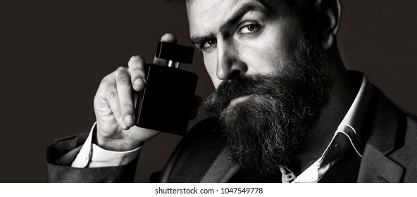 Man perfume, fragrance. Fashion perfume bottle. Perfume or cologne bottle. Male fragrance and perfumery, cosmetics. Bearded man holding up bottle of perfume. Fashion cologne bottle. Black and white.