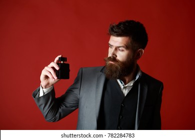 Man perfume, fragrance. Masculine perfume. Perfume or cologne bottle. Male fragrance and perfumery, cosmetics. Bearded man holding up bottle of perfume. Fashion cologne bottle.