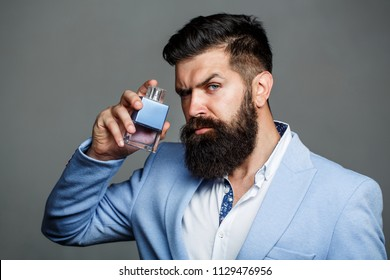 Man perfume, fragrance. Masculine perfume. Male fragrance and perfumery, cosmetics. Bearded man holding up bottle of perfume. Fashion cologne bottle. Bearded male prefers expensive fragrance smell.