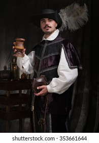 A man in period costume and hat raises a glass of wine.
