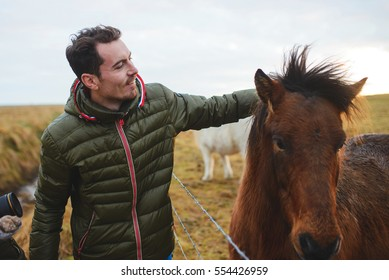 man petting red horse at sunset
