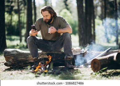 Man with phone by bonfire in forest