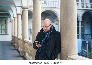 man with a phone at the column.